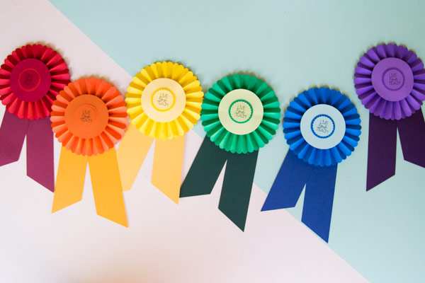 Use your Cricut to create these easy prize ribbons. Attach a gift card or use them as a fun embellishment to a gift bag. These prize ribbons were so easy to make with my Cricut. #CricutMade #RainbowCraft #PrizeRibbon