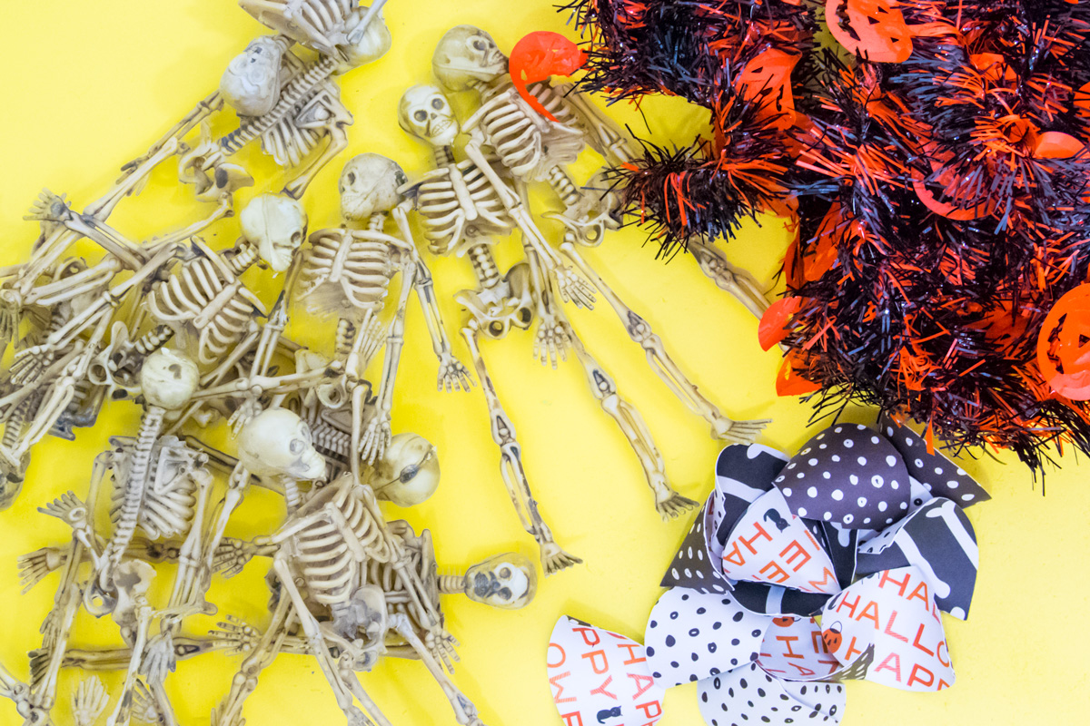 Make your dollar store purchases go even further with thiseasy halloween skeleton garland. They're ready for the party with their adorable mini party hats. #halloween #hotglue #cricutmade