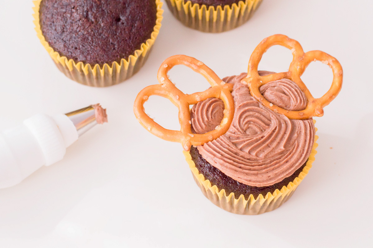 cupcake with brown frosting and pretzel antlers