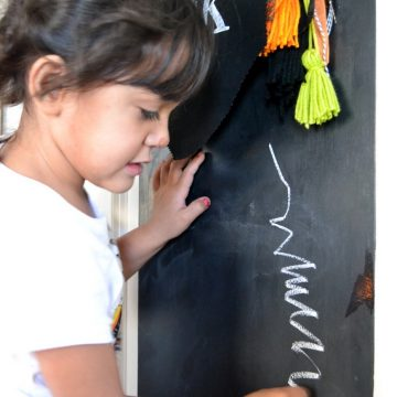Use a chalkboard door to create and art center for kids on seelindsay.com