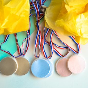 Create these DIY Olympic Medals. The perfect kids craft to celebrate the excitement of the Olympics.