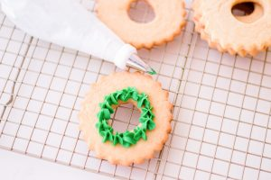 piping green frosting on wreath cookie