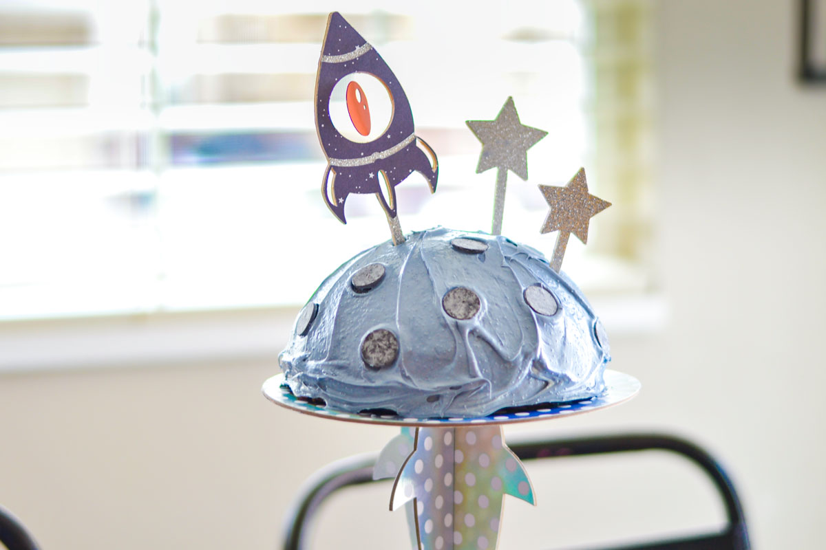 Make your own out of this world cake stand using your Cricut Maker. Cut all the pieces using your Cricut Knife Blade and then adhere the iridescent cardstock to it by using your Xyron Creative Station. #cricutmade #cricutmaker #diypartydecor #partydecorations #cakestand #outerspaceparty #spaceshipparty