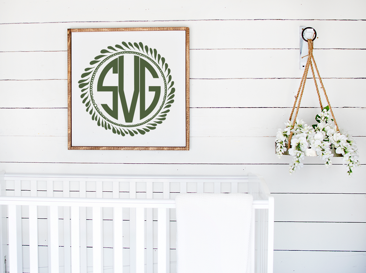 monogram wreath framed  above a  white crib
